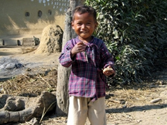 A happy Tharu boy smiles at the influx of visitors to his village; near Chitwan National Park