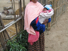 A Tharu teenaged mother shows off her newborn baby