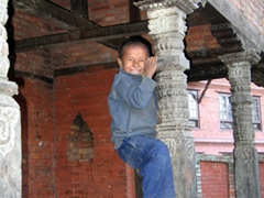A young boy shows off his climbing skills; Bhaktapur