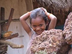 Gadhaba girl posing from behind a stone wall