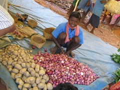 Young vendor selling sweet onions at the Maria Tribe's weekly Mardoom market