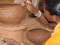 A tribal woman working on the finishing touches of a clay bowl, Tribal Artisans Organization