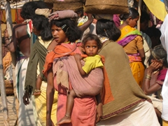 Young Dongariya tribesgirls carrying their babies and purchases