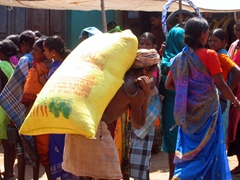 Village elder struggles to carry a heavy load of rice