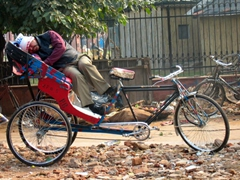 A tired rickshaw driver takes a quick nap while waiting on customers; Delhi