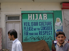 A sign posted in Skardu urges women to consider wearing the hijab as a show of respect for the culture