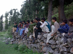 Naltar fans climb atop a rock wall to watch the polo match