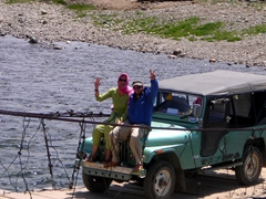 Sitting on the hood of our jeep as Jan drives us across a bridge in Deosai National Park