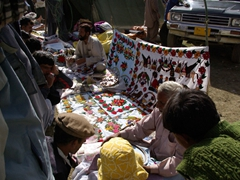 An old man demonstrates embroidery to an attentive and curious crowd