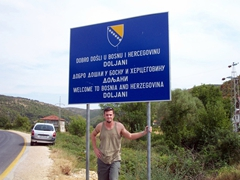 "Robby under a ""Welcome to Bosnia"" signpost"