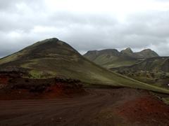 Red road cutting through green hills leading down to Landmannalaugar