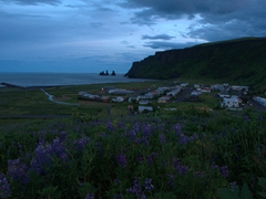 Midnight view of Vík (with Reynisdrangar pinnacles in the background)
