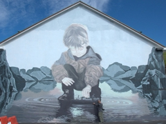 Robby is dwarfted by a massive mural painted on a harbor building; Heimaey Island