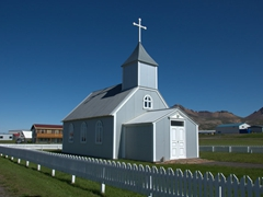 A white picket fence surrounds a church in Bakkagerði