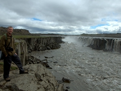 Robby poses next to Selfoss (upstream of Dettifoss), an interesting horse shoe shaped waterfall