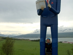 Becky in between the legs of a statue at the  Icelandic Folk and Outsider Art Museum; Akureyri