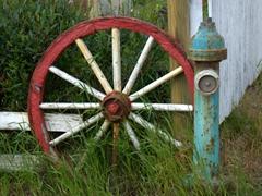 Colorful wagon wheel and fire hydrant; Hólmavík