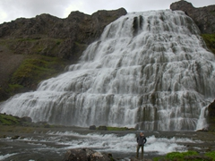 Becky appears miniscule at the bottom of her favorite waterfall in Iceland, the beautiful Dynjandi