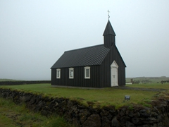 A foggy morning view of Búðir church, a tiny black 19th Century wooden church built on a lava field