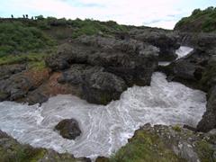 Barnafossar gushes wildly through a narrow volcanic canyon