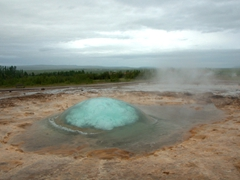 Anticipation mounts as a bubble forms mere moments before the Strokkur geyser erupts