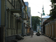 An elderly Estonian woman strolls down a scenic side street in Pärnu