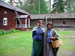 Two smiling Finnish guides dressed in traditional costume. During the summer months, they showcase folk-dancing and crafts at the Seurasaari Open Air Museum