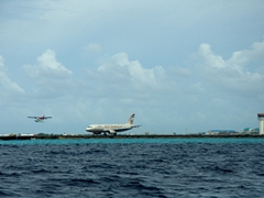 A seaplane takes off after a jetliner lands at the busy airport island of Hulhule