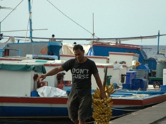 A Maldivian struggles to carry his heavy load of bananas by the Malé waterfront