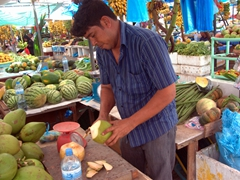 A vendor preparing our coconut drinks at the Male fruit and vegetable market