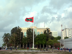 A massive Maldives flag waving over Jumhooree Maidan; Male