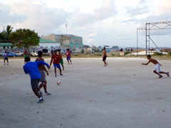 Maldivians playing soccer at dusk; Male