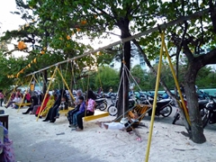 Swings are occupied by Male residents at dusk; near the Artificial Beach
