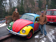 Jim and Robby strike a pose next to a colorful VW bug