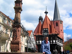 "Becky strikes a pose at Michelstadt's main market square with the town's four landmarks visible (the city fountain, the pink New Town Hall, the Pfarrkirche aka ""reformed church"" whose red brick steeple is in the background, and the half-timbered Old Town Hall"