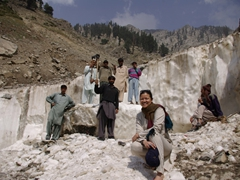 Becky poses before some axe-wielding workers who carve out ice blocks to sell in Chitral
