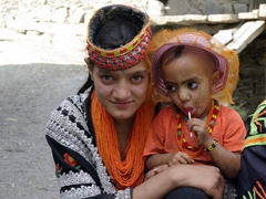 A Kalasha girl holds onto her sister who is too young to don the traditional outfit
