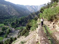 Saeed jogs alongside the water canal to catch up with us; Birir Valley