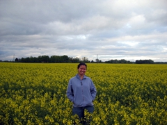 Becky standing in the middle of a rape field, Lithuanian countryside