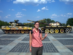 Becky flashing the peace sign in front of 'flower' graffiti war tanks; near the Mother Motherland Monument