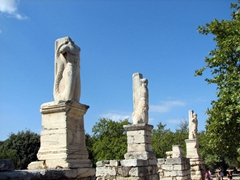 Three serpent tailed statues of giants and tritons stand guard in front of the Odeon of Agrippa, a theatre that is in ruins; Ancient Agora
