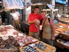 A local fish vendor holds up fresh octopus; Athens Fish Market