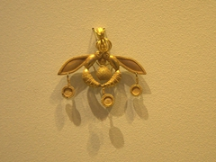 Gold bee pendant showcasing two bees carrying a drop of honey; Heraklion Archeological Museum