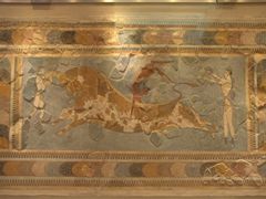 "The famous ""bull leaping"" fresco with a double jointed acrobat performing a somersault across the back of a charging bull"