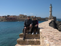 Bob & Ann posing on the sea wall in front of the restored Venetian lighthouse at the entrance to the harbor; Chania