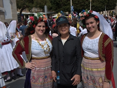 Ann is invited to strike a pose next to two ladies in traditional Greek outfits