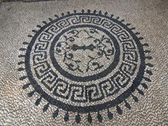 "This pebble flooring, known as ""hohlaki"", consists of black and white pebbles set into the ground; Captain's House Bar"