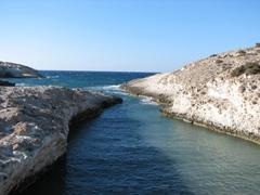 A narrow channel brings gushing water into the northern coast; Sarakiniko Beach