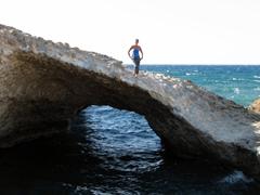 Becky strikes a pose on a natural arch; Sarakiniko Beach