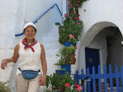 Ann poses beside a flower potted staircase and the entrance to a typical home in Lefkes